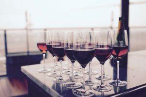 ワイングラスに入ったワインを沢山テーブルに並べている