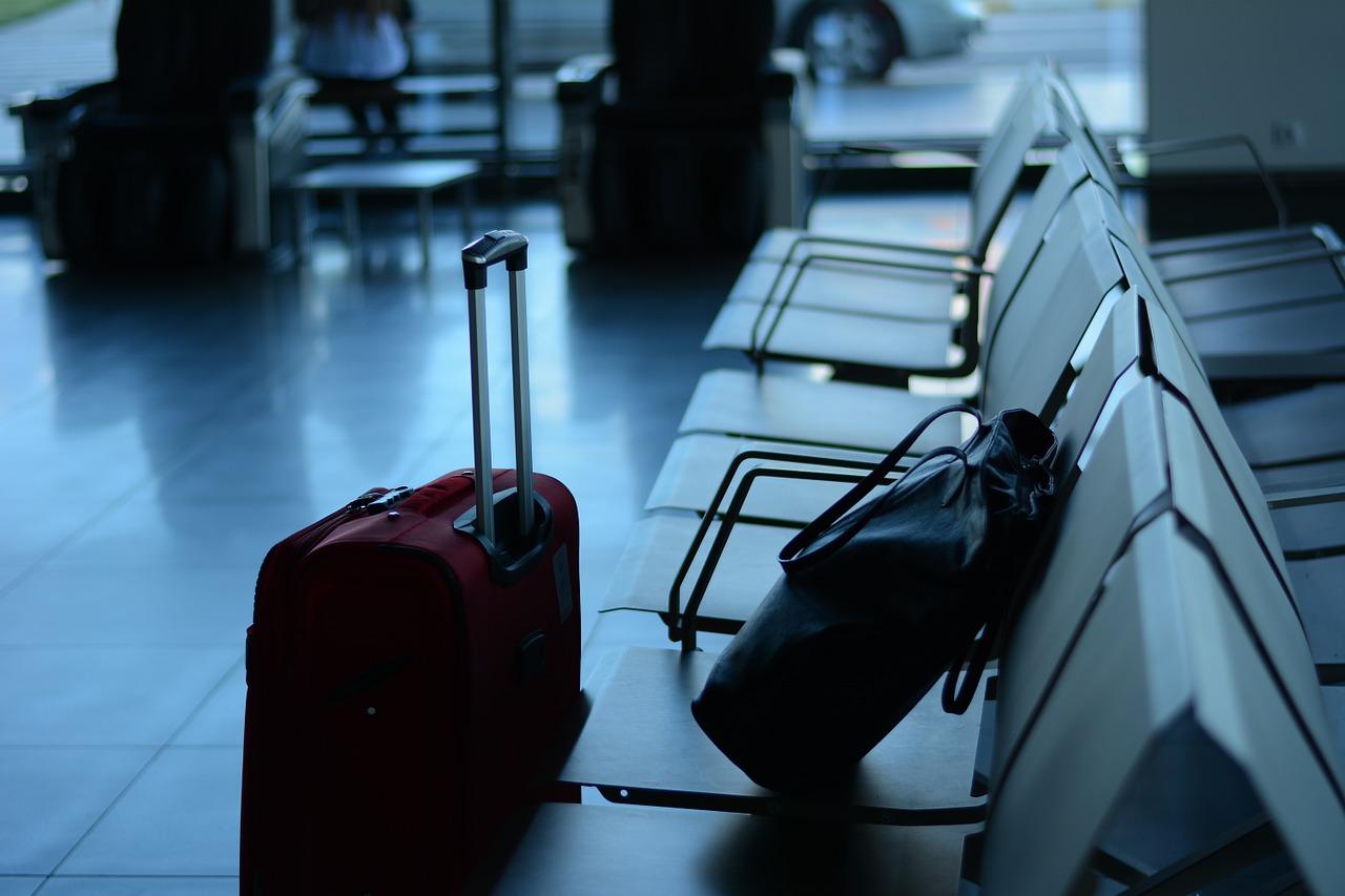 空港の椅子に置かれた荷物と床に置かれたスーツケース